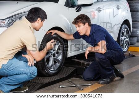 Male customer discussing with mechanic repairing car at repair shop - stock photo