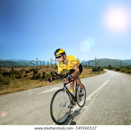 Male cyclist riding a bike on an open road on a sunny day, shot with a tilt and shift lens - stock photo
