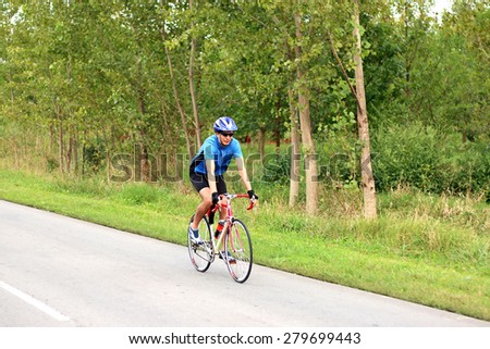 male cyclist riding a bike on an road - stock photo