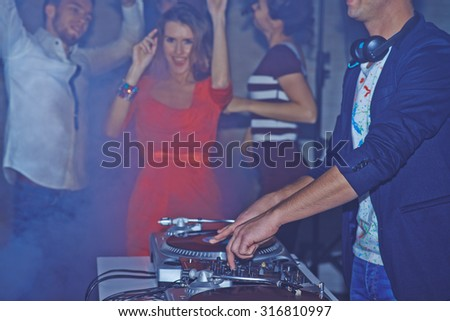 Male deejay adjusting sound on background of dancing friends - stock photo
