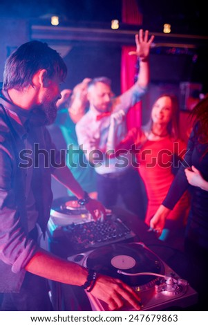 Male deejay adjusting sound with group of dancing friends near by - stock photo
