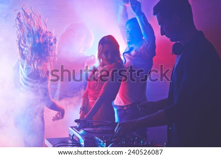 Male deejay mixing sounds with energetic girls and guy dancing on background - stock photo