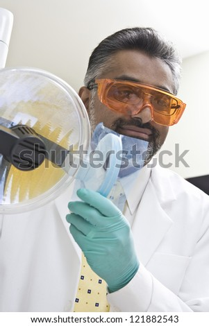 Male dentist adjusting lamp for treatment in clinic - stock photo