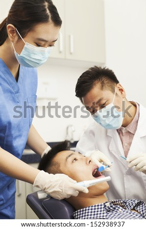 Male Dentist Examining Male Patient - stock photo