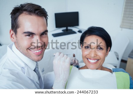 Male dentist examining womans teeth in the dentists chair - stock photo