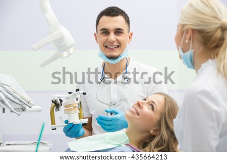 Male dentist in the dental cabinet. He is in the white uniform with blue latex gloves, blue mask, binocular loupes. He sits on the chair and holds an articulator with teeth mould.  - stock photo