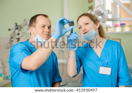 Male dentist showing an x-ray to female assistant at dental clinic office. Doctors wearing gloves and masks. Teeth care and tooth health. - stock photo