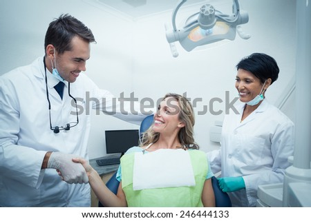 Male dentist with assistant shaking hands with woman in the dentists chair - stock photo