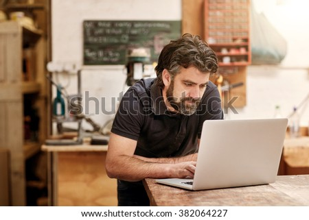 Male designer and craftsman with a rugged beard, working on his laptop at his workbench, in his studio workshop - stock photo