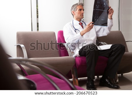 Male doctor analyzing mri scan. - stock photo