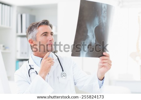 Male doctor analyzing x-ray in clinic - stock photo