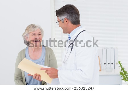 Male doctor and female patient conversing over reports in clinic - stock photo