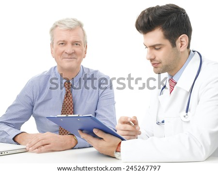Male doctor and old patient analyzing result of test while sitting against white background. - stock photo