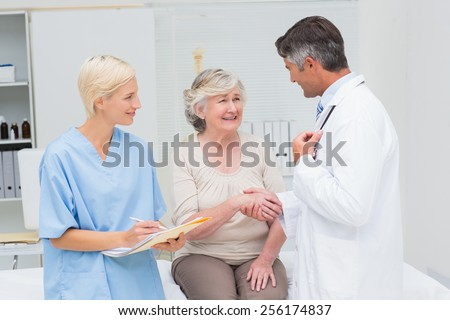 Male doctor and senior patient shaking hands while nurse writing reports in clinic - stock photo