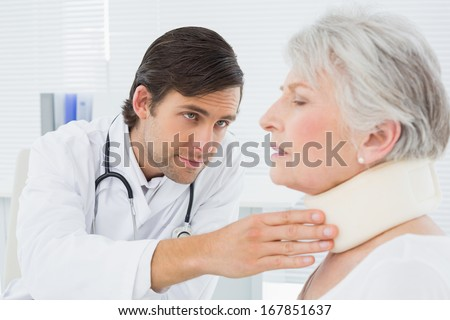 Male doctor examining a senior patient's neck in the medical office - stock photo