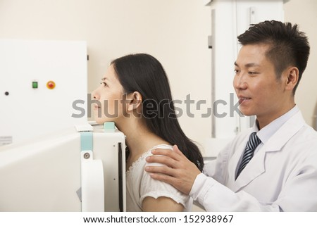 Male Doctor Examining Female Patient's Mid Section With X-ray Machine - stock photo