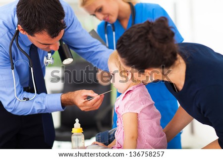 male doctor examining little girl with mother in office - stock photo