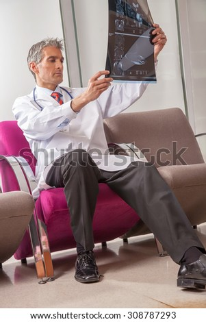 Male doctor examining x-ray scan film in hospital structure. - stock photo
