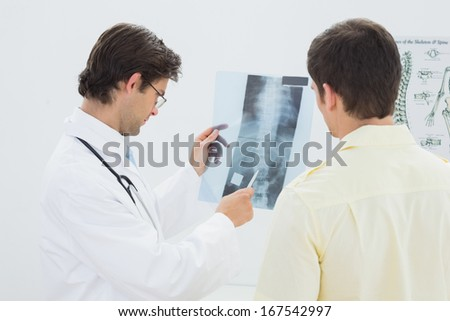 Male doctor explaining spine x-ray to patient in the medical office - stock photo