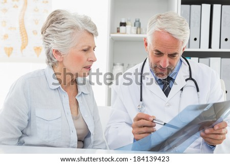Male doctor explaining x-ray report to senior patient in the medical office - stock photo