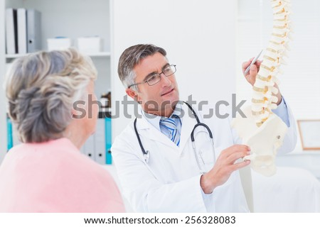 Male doctor explaning anatomical spine to senior woman in clinic - stock photo