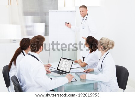 Male doctor giving presentation on flipchart to colleagues in hospital - stock photo