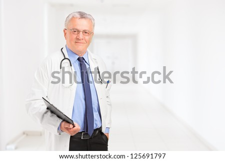 Male doctor holding a clipboard and standing in a hospital hall - stock photo