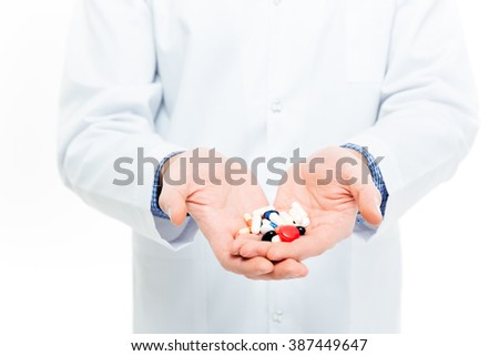 Male doctor holding pills isolated on a white background - stock photo
