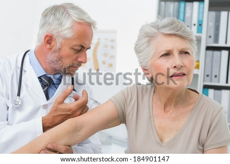 Male doctor injecting senior female patient at the medical office - stock photo
