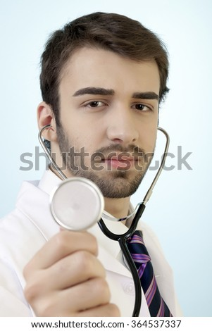 Male doctor is checking her patience with focus on stethoscope in confidence against a blue vignette background. - stock photo