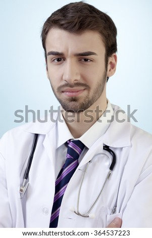 Male doctor is posing with confidence in front of blue vignette background. - stock photo