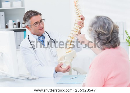 Male doctor showing anatomical spine while female patient touching it in clinic - stock photo