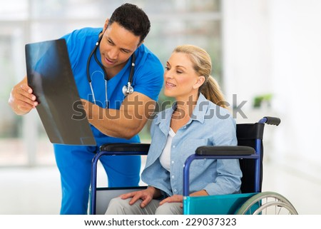 male doctor showing x-ray report to senior disabled patient in hospital - stock photo
