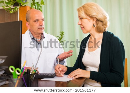 Male doctor talking with mature patient in clinic office - stock photo