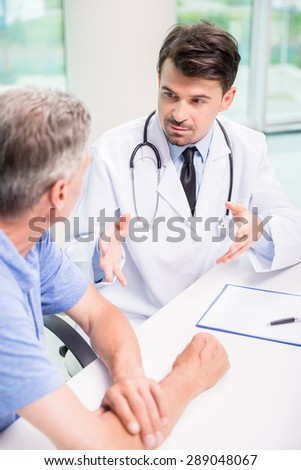 Male doctor talking with patient seriously at clinic. - stock photo