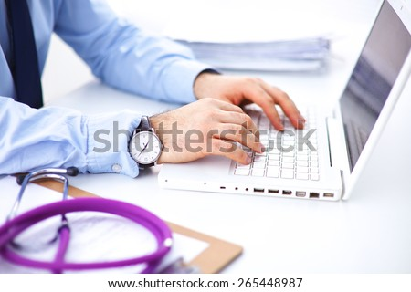 Male doctor using a laptop, sitting at his desk  - stock photo