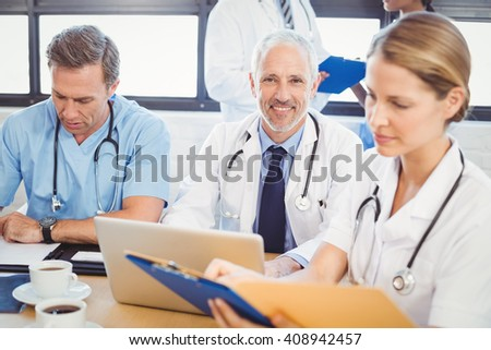 Male doctor using laptop in conference room and colleagues working beside him - stock photo