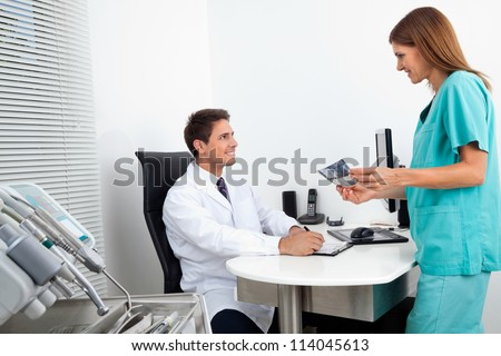 Male doctor with assistant holding X-ray report at office desk - stock photo