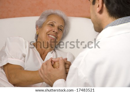 Male doctor with elderly woman patient - stock photo