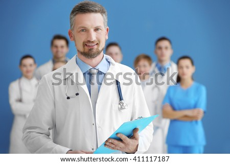 Male doctor with medical team in hospital - stock photo