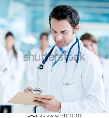 Male doctor writing medical history at the hospital  - stock photo