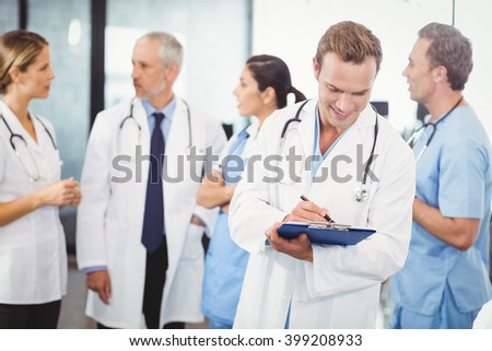 Male doctor writing on clipboard and colleagues standing behind and discussing in hospital - stock photo