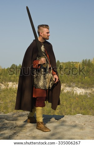 Male dressed in Barbarian style with sword in the mountains  - stock photo