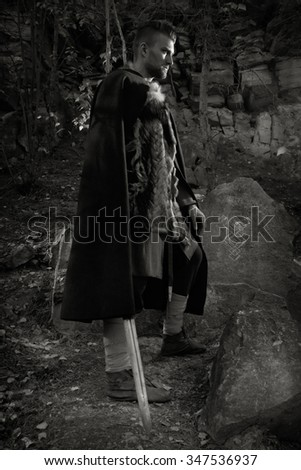 Male dressed in Barbarian style with sword in the mountains