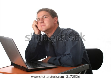 Male dressed in black sitting at office desk with laptop. Isolated; Dreaming - stock photo