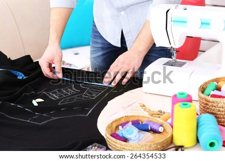 Male dressmaker drawing line on fabric on table close-up - stock photo
