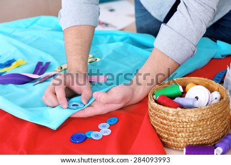 Male dressmaker tailor fabric on table - stock photo