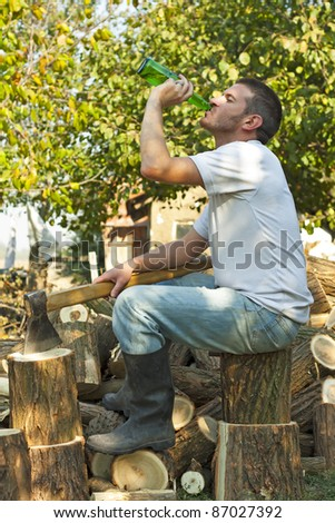 Male drinking beer whilst taking a relaxing break from splitting logs in the dappled autumn sunshine - stock photo