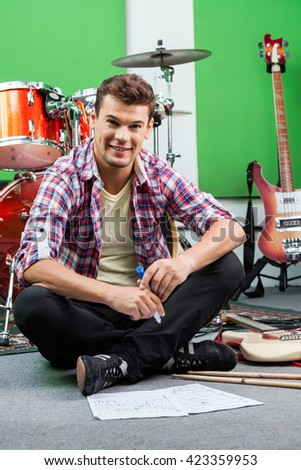 Male Drummer Holding Sketch Pen While Sitting On Floor - stock photo