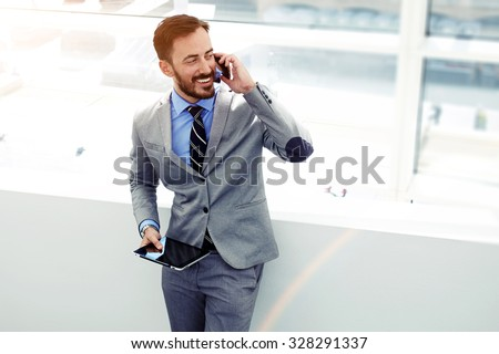 Male economist talking on cell telephone while standing with touch pad in modern interior with copy space area, young successful men entrepreneur speaking on mobile phone during work on digital tablet  - stock photo